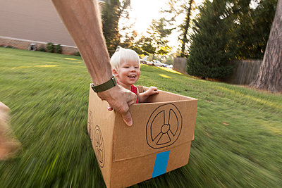 Father pulling son across grass in cardboard car - p1480m2229678 by Brian W. Downs
