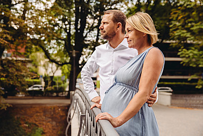 Mature pregnant couple standing at bridge in park - p300m2042746 by Mareen Fischinger