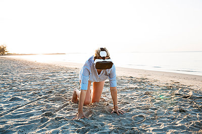 Thailand, woman using virtual reality glasses on the beach in the morning light - p300m2080383 by Epiximages