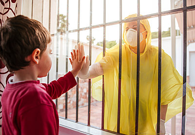 Boy touching mother's hand wearing protective clothing behind windowpane - p300m2189257 by DREAMSTOCK1982