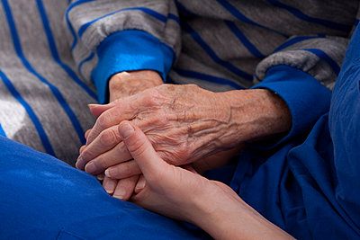 Close up of granddaughter holding hands of grandmother - p555m1408863 by Shestock