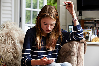 Teenage looking at cellphone and playing with her hair - p924m734584f by Sverre Haugland