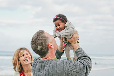 Cheerful parents playing with baby girl at beach against sky - p1166m1473699 by Cavan Images
