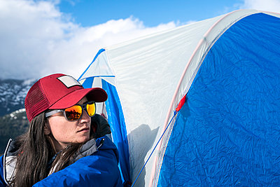 Portrait of a woman in a red hat sitting in front of her tent at base camp, Mt. Baker - p1166m2157170 by Cavan Images