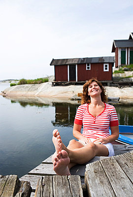 A woman sitting on a jetty in the archipelago of Stockholm Sweden. - p31219959f by Plattform