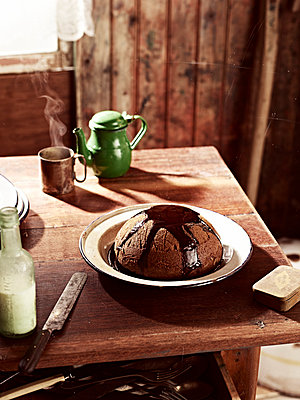 Rustic table with dish of steamed treacle pudding - p429m1012832f by BRETT STEVENS