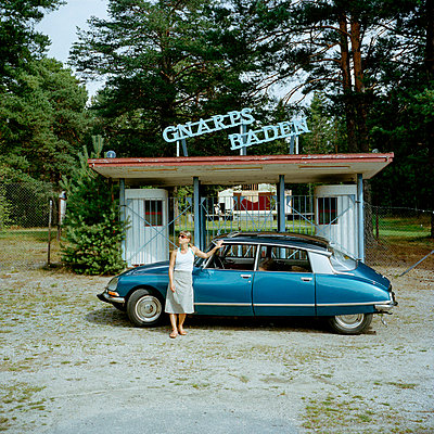 Women standing in front of vintage car with abandoned amusement car in background - p528m696674 by Johan Willner