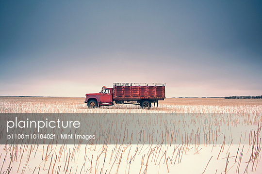 A farm truck in a stubble field surrounded by open space.  - p1100m1018402f by Mint Images