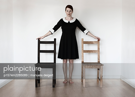 Woman between two chairs - p1574m2285089 by manuela deigert