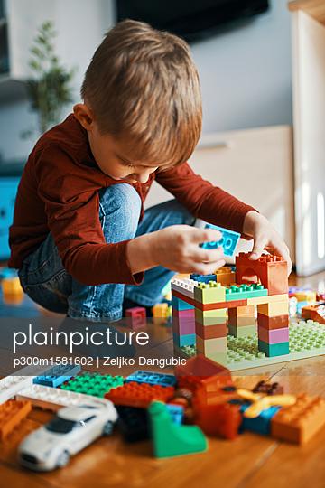 Little boy playing with building bricks on the floor at home - p300m1581602 von Zeljko Dangubic