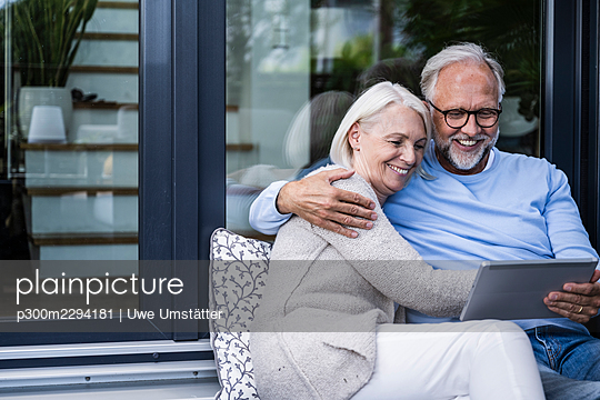 Smiling man using digital tablet while sitting with arm around woman at balcony - p300m2294181 by Uwe Umstätter