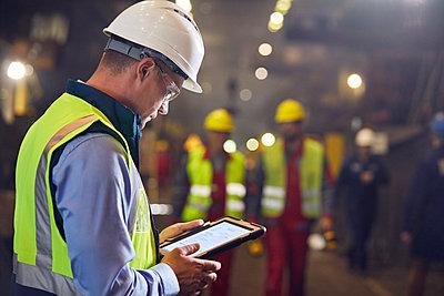 Steelworker using digital tablet in steel mill - p1023m1519912 by Agnieszka Olek