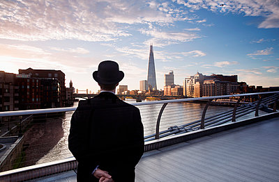Rear view of man wearing black coat and Bowler hat standing on Millennium Bridge over the River Thames in London, England, the Shard skyscraper in the distance. - p1100m1570960 by Mint Images