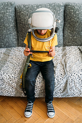 Boy playing video game on a games console, wearing space hat - p300m2103106 by Jose Luis CARRASCOSA