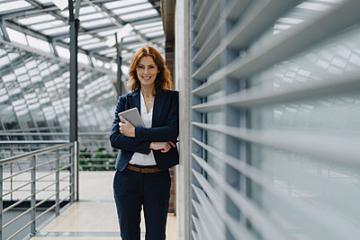 Portrait of a smiling businesswoman holding a tablet in a modern office building - p300m2156334 by Joseffson