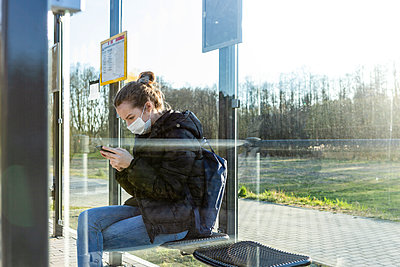 Girl with mask waiting at bus stop, using smartphone - p300m2180800 by Julia Otto