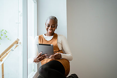 Smiling woman looking at digital tablet while sitting by window in living room - p300m2276371 by Rafa Cortés