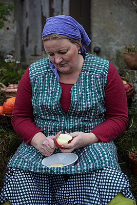 Farmer's wife is peeling an apple - p502m892132 by Tomas Adel