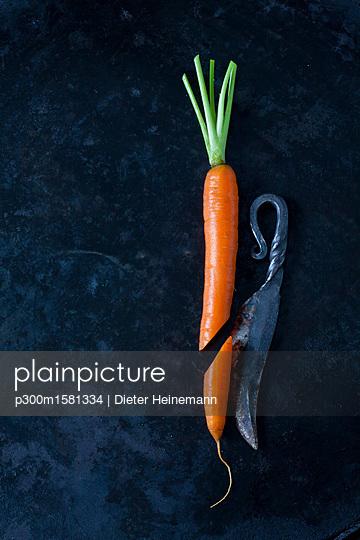 Sliced carrot an an old knife on dark ground - p300m1581334 von Dieter Heinemann