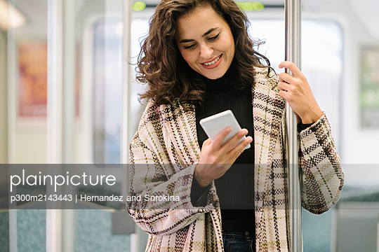 Smiling young woman using smartphone on a subway - p300m2143443 by Hernandez and Sorokina