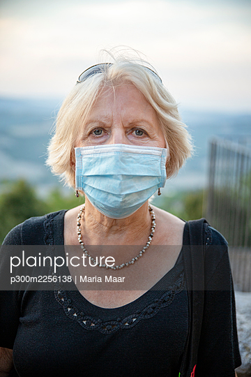 Senior woman wearing protective face mask staring while standing outdoors during COVID-19 - p300m2256138 by Maria Maar