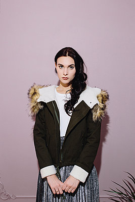 Portrait of a girl in a jacket with a fur collar on pink background - p1363m1332298 by Valery Skurydin