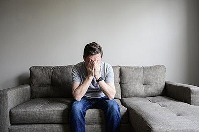 Depressed mature man sitting on couch - p1427m2109883 by Dermot Conlan