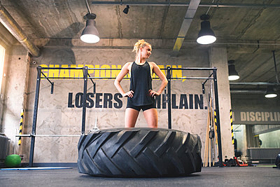 Young woman exercising with tractor tyre in gym - p300m1469628 by HalfPoint