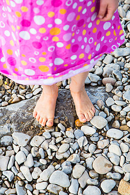 Feet of little girl standing on pebbles at riverside - p300m980303f by Larissa Veronesi