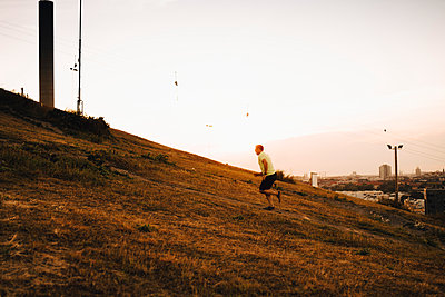 Sportsman running on land during sunset - p426m2270571 by Maskot