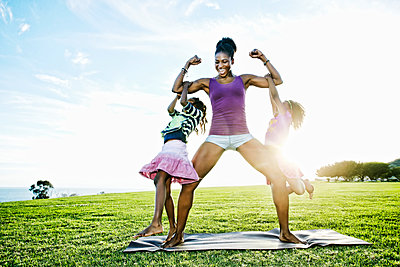 Woman lifting children with biceps in park - p555m1411316 by Peathegee Inc
