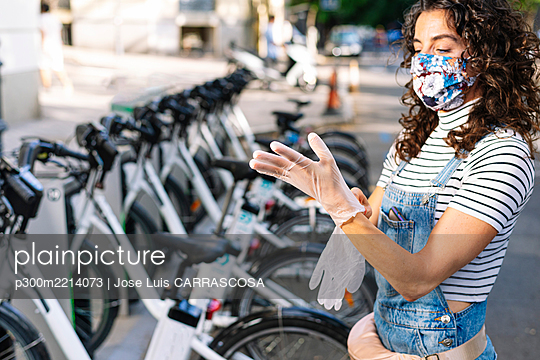 Mature woman wearing gloves at electric bicycle parking station during COVID-19 - p300m2214073 by Jose Luis CARRASCOSA