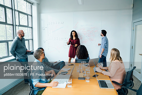 Business people using whiteboard in meeting - p555m1503975 by FS Productions
