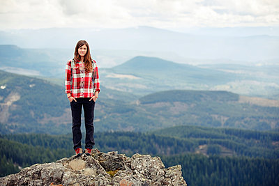 Portrait of smiling woman standing on top of mountain against cloudy sky - p1166m1227824 by Cavan Images