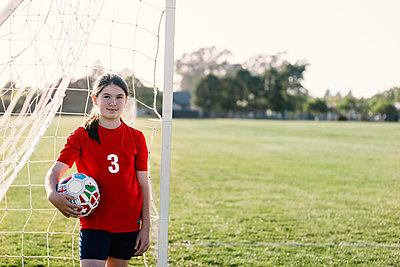 Portrait of girl wearing red soccer uniform standing against goal post during sunny day - p1166m2060441 by Cavan Images