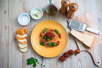 Spaghetti with cherry tomatoes and basil on a plate - p300m1536278 by Giorgio Fochesato