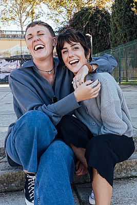 two young women sitting on stair hugging and laughing, Seville, Spain - p300m2252415 von Julio Rodriguez