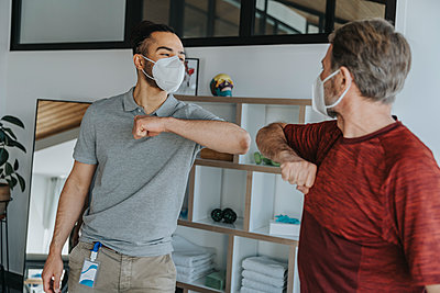 Mature male patient doing elbow bump with physiotherapist during pandemic - p300m2275959 by Mareen Fischinger