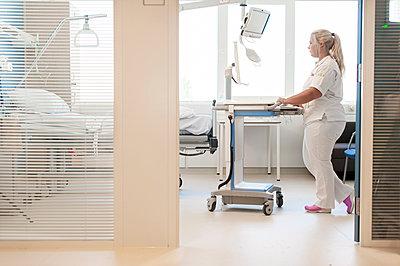 Nurse on hospital ward pushing trolley - p429m1197769 by Arno Masse