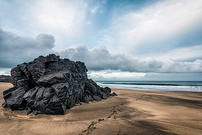 Footprints on beach near rock formation - p555m1491146 by Patrick Lienin
