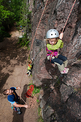 Father protecting climbing girl - p575m696326f by Fredrik Schlyter