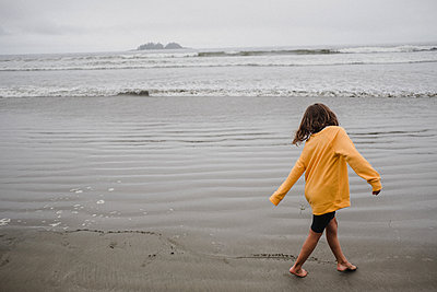 Girl playing on beach, Tofino, Canada - p924m2018644 by Kymberlie Dozois Photography