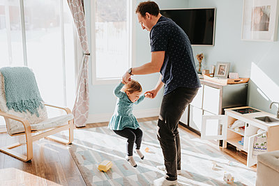 Father playing with toddler daughter on living room rug - p924m2077774 by Sara Monika
