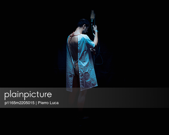 Einsamer Patient steht in dunkler Umgebung  - p1165m2205015 von Pierro Luca
