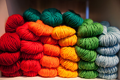 Colorful yarn neatly stacked on a shelf - p1106m1111175 by Angela DeCenzo