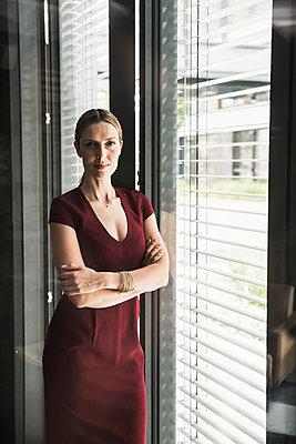 Woman wearing burgundy dress standing at the window - p300m2023676 von Uwe Umstätter