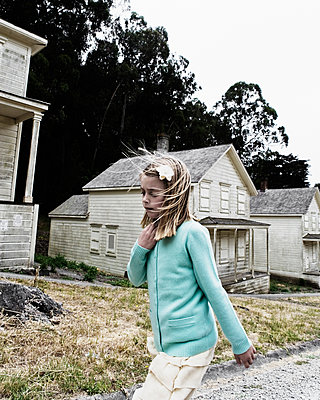A young girl walking in front of old abandoned houses. - p343m1554696 by Ron Koeberer