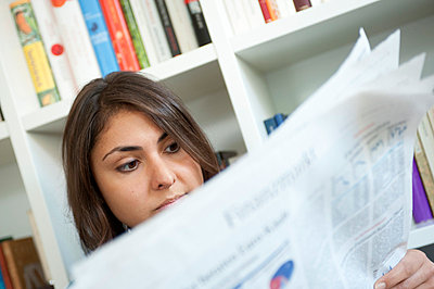 Student reading newspaper - p427m731769 by Ralf Mohr