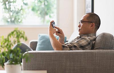 Korean man using cell phone on sofa - p555m1414365 by JGI/Tom Grill