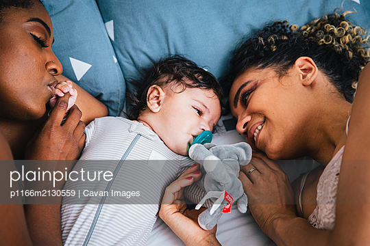 High angle view of loving mothers lying with cute son on bed at home - p1166m2130559 by Cavan Images